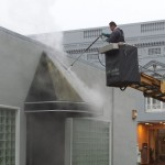 Worker power washing business's awning